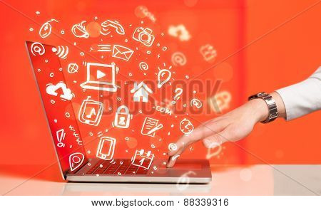 Hand writing on notebook computer with media icons and symbols comming out