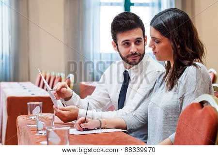 Business Couple Reviewing Work In Conference Room.