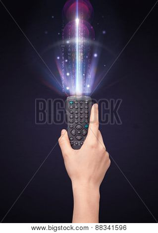 Hand holding a remote control, shining numbers and letters coming out of it