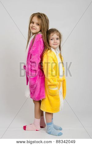 Two Girls In Dressing Gowns Stand Back To Back