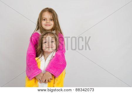 Girl In Bathrobe Hugging Her Sister A Bathrobe