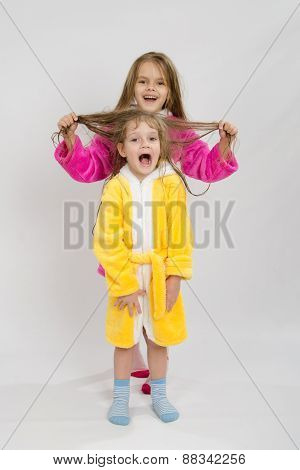 Girl Holding Her Sisters Wet Hair