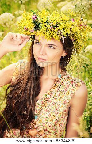 Romantic girl in a wreath of wild flowers in a field. Summer life. Beauty.
