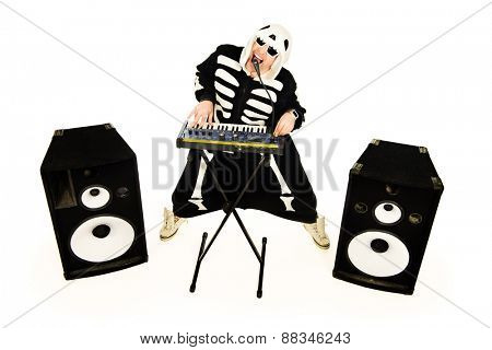 Rock musician in a skeleton costume playing the synthesizer and singing. Music. Halloween.