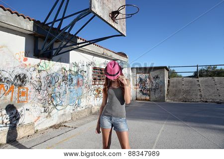 teenager with hat in the playground with graffiti