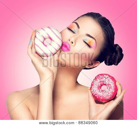 Beauty fashion model girl taking kissing colorful donuts. Funny joyful Vogue styled woman choosing sweets on pink background. Diet, dieting concept. Junk food, Slimming, weight loss