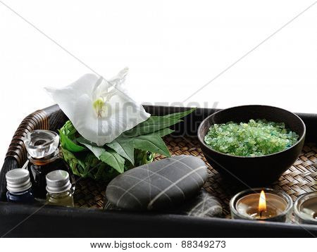 white flower with candle and massage stones on platter, isolated on white