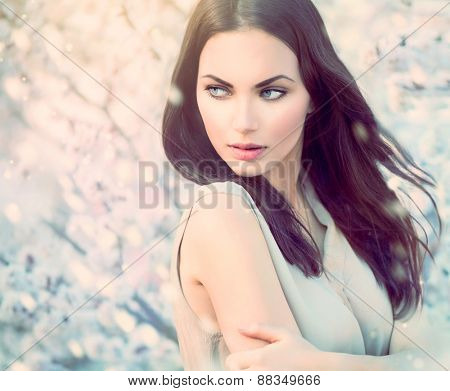 Fashion girl outdoor portrait in blooming trees. Beauty spring Romantic woman in flowers. Sensual Lady. Beautiful Woman Enjoying Nature. Romantic beauty in fantasy orchard