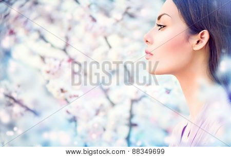 Spring fashion girl outdoor portrait in blooming trees. Beauty Romantic woman in flowers. Sensual Lady. Beautiful Woman Enjoying Nature. Romantic beauty in fantasy orchard