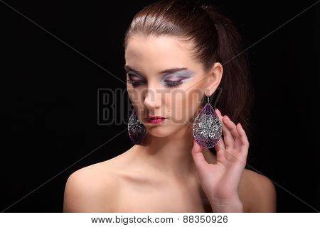 Beautiful girl with creative colorful makeup on a dark background