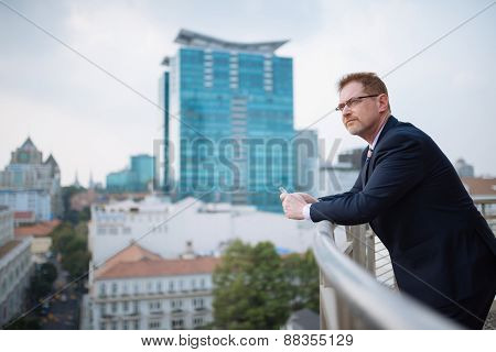 Pensive businessman with cellphone