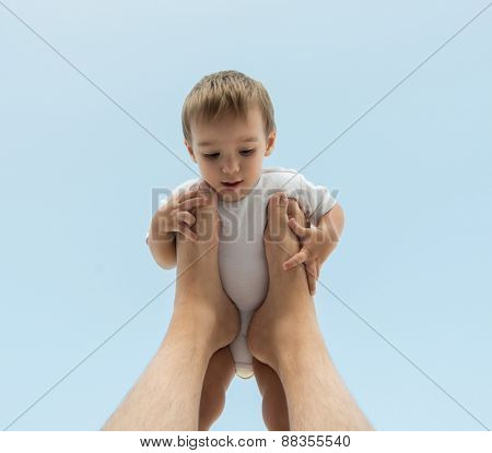 Father holding baby son on his legs in air