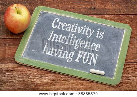 Creativity is intelligence having fun - inspirational words  on a slate blackboard against red barn wood