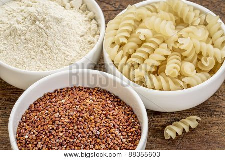 gluten free quinoa grain, flour and pasta on small ceramic bowls - healthy eating concept
