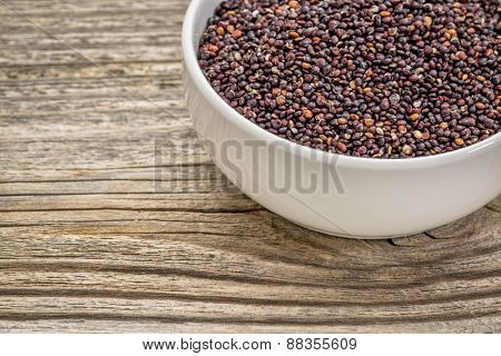 gluten free, black quinoa grain in a small, ceramic bowl against grained wood