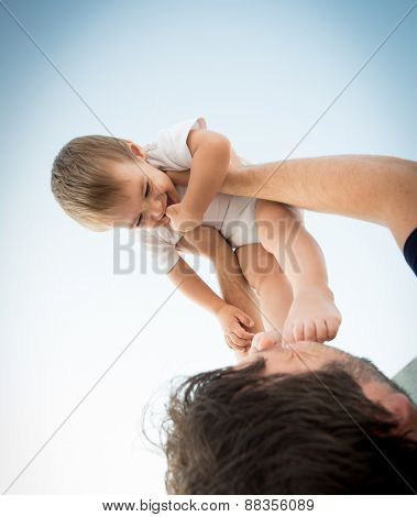 Father holding his baby son in air on legs