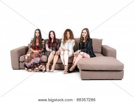 Four attractive women on sitting on sofa