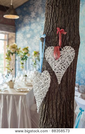 Two Wicker Hearts Hanging On Tree In Wedding Hall.