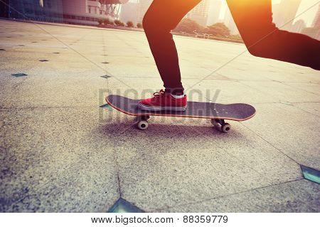woman skateboarder legs skateboarding at sunrise city
