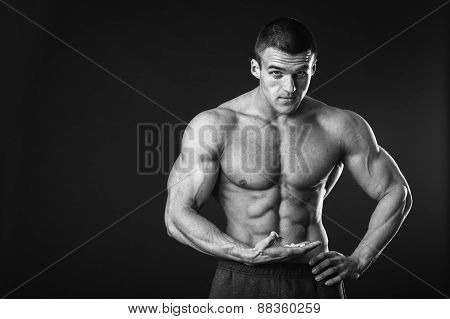 Muscular young man posing in the studio on a black white background.