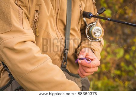 Fisherman on the river bank. Autumn fishing. Fisherman in his hand holding spinning