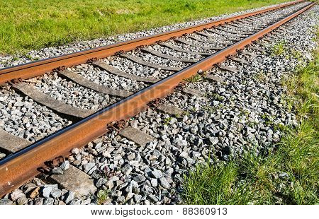 Rusty Orange Colored Railroad Rails Diagonally In The Image