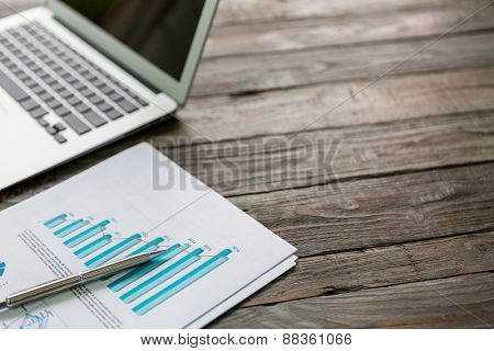 Financial charts on the table with laptop