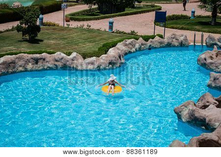 Beautiful Young Woman Sitting On Life Preserver In Pool