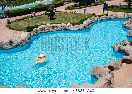 Beautiful Young Woman Swim On Life Preserver In Pool