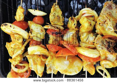 fresh raw roast shish kebab on barbecue grill grid coocked over hot charcoal