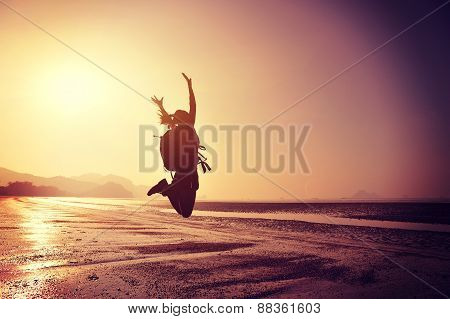 cheering young woman hiker jumping on sunrise beach