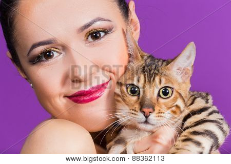 Young beautiful girl posing in the studio, she is holding a Bengal cat