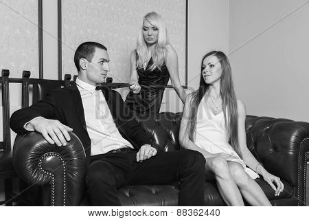 A guy and two girls in the room, tense. Group young people enjoy the evening.