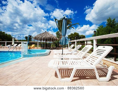 Beach chairs side swimming pool, Greece