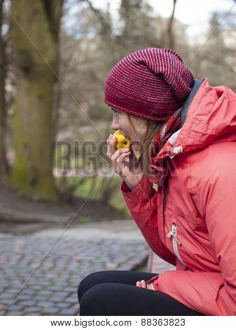 A Young Girl Eats An Apple.