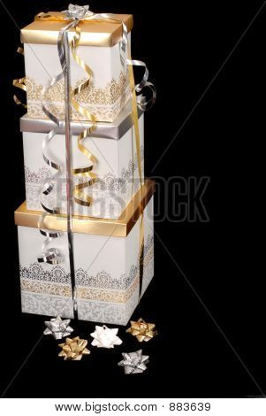 Three Silver And Gold Wrapped Christmas Presents With Bows