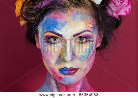Beautiful young girl with a painted face with a flower in her hair.