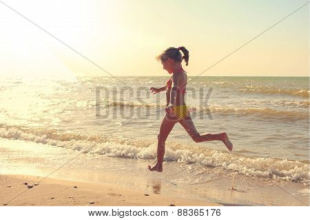 Girl in swimsuit runs along the shore of the sea. Toned image