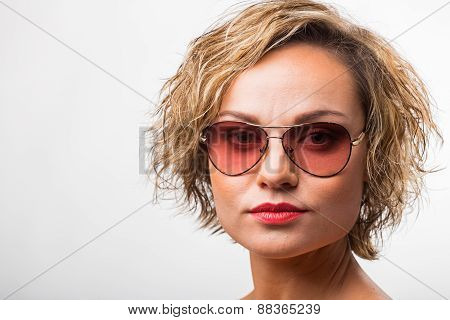 Gorgeous blonde posing in the studio. Beautiful blonde in sunglasses.