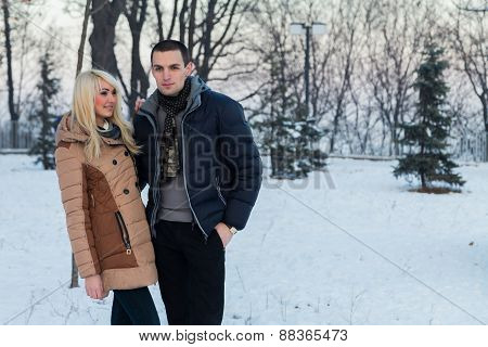 Portrait of young happy couple posing outdoors in winter