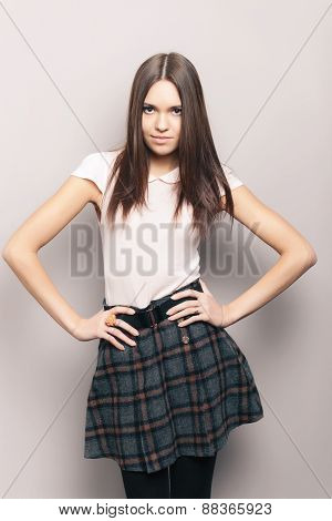 Young stylish beautiful brunette woman posing indoors against wall