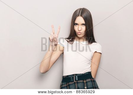 Young beautiful brunette woman posing indoors against wall with air kiss and victory gesture