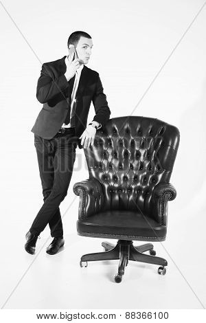 Male businessman sitting on a black leather chair on a white background.