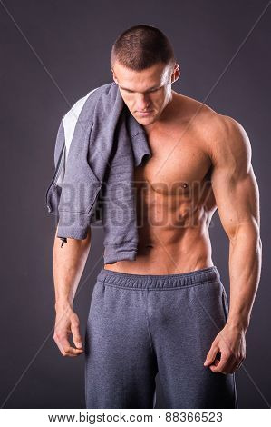 Handsome, muscular man in sportswear posing on a dark background