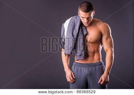Handsome, muscular man in sportswear posing on a dark background
