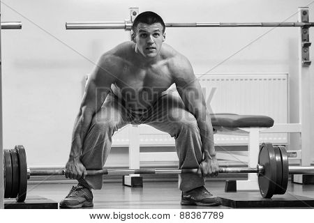 A man performs an exercise with a barbell. Young weightlifter in the gym