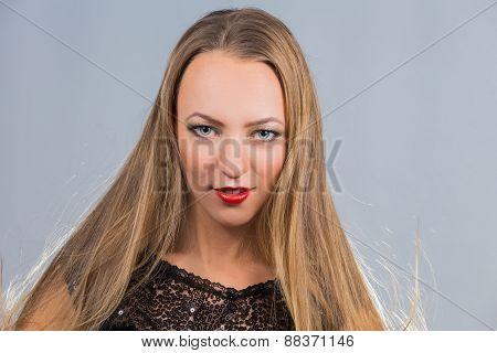 Cute blonde girl posing in the studio. Beautiful blue eyes