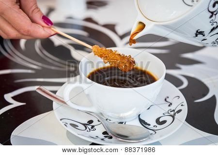 Coffee from a beautiful black and white teapot, pour into a cup on the table designer.