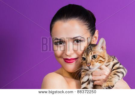 Young beautiful girl in the studio holding a Bengal cat.