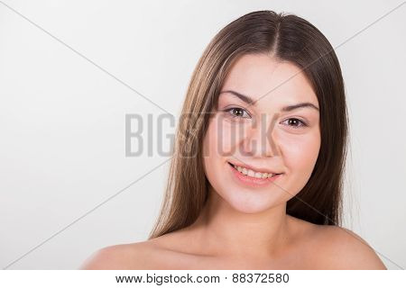 Portrait of a gentle, beautiful brunette on a light background.